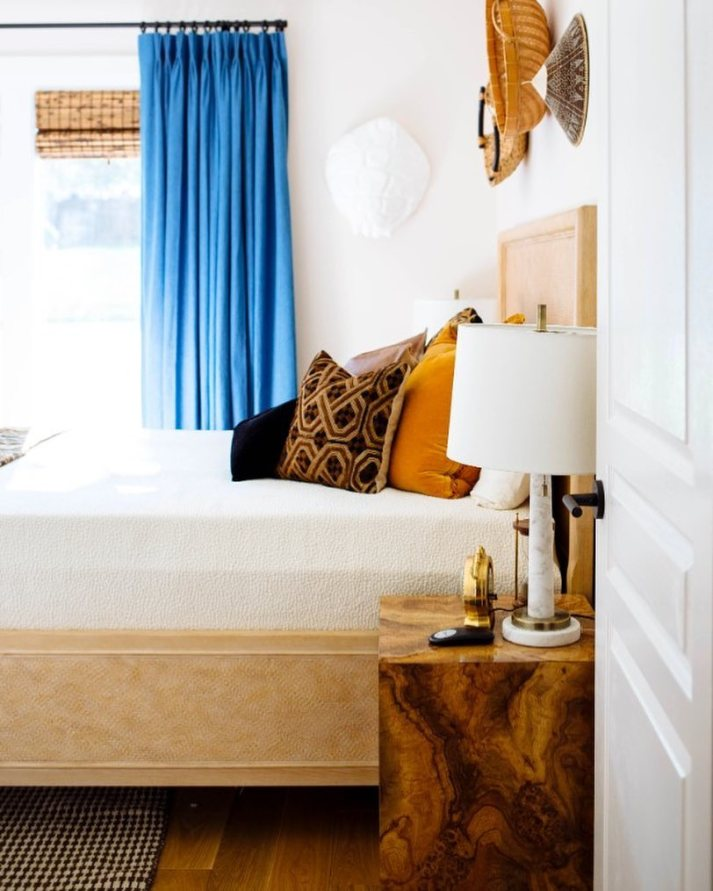 guest bedroom makeover with burl wood nightstand, patterned throw pillows and woven wood shades with blue curtains on windows