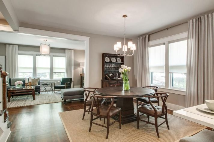 Upgraded Neutral dining room with round table and roller shades featuring open floor plan with open view to living room