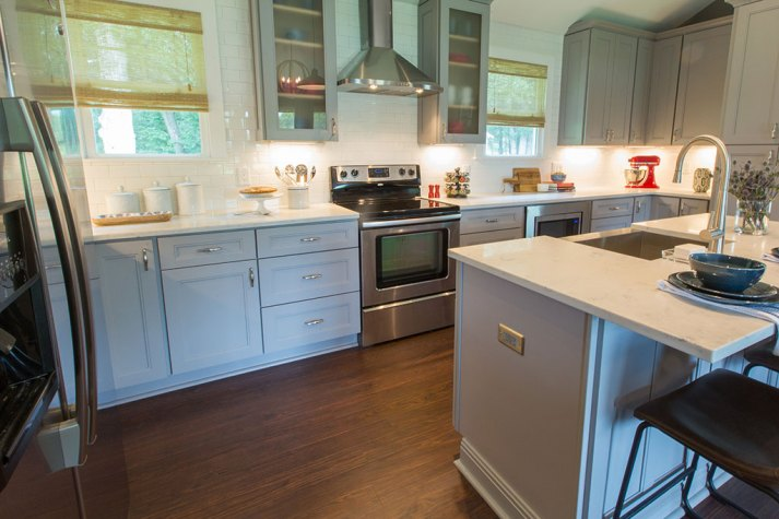 detail shot of property brothers' kitchen with dark wood floors and woven wood shades on windows on either side of stove