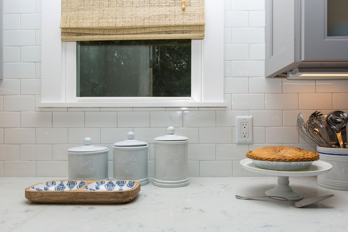 White kitchen with quartz countertops, white subway tile and window with woven bamboo shade