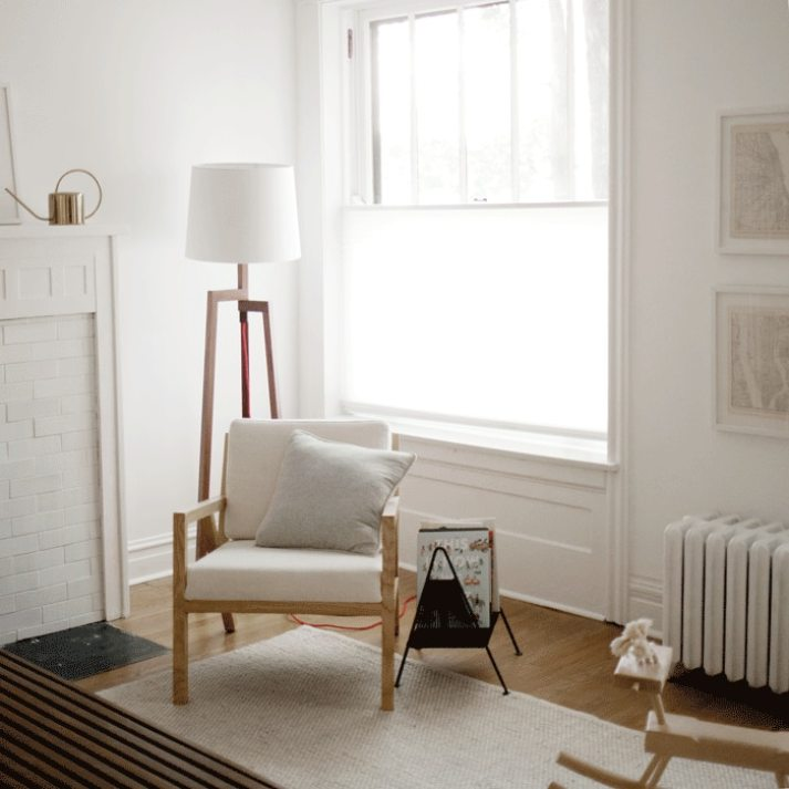 corner of living room with scandinavian inspired furniture and white cellular shade covering bottom half of windows