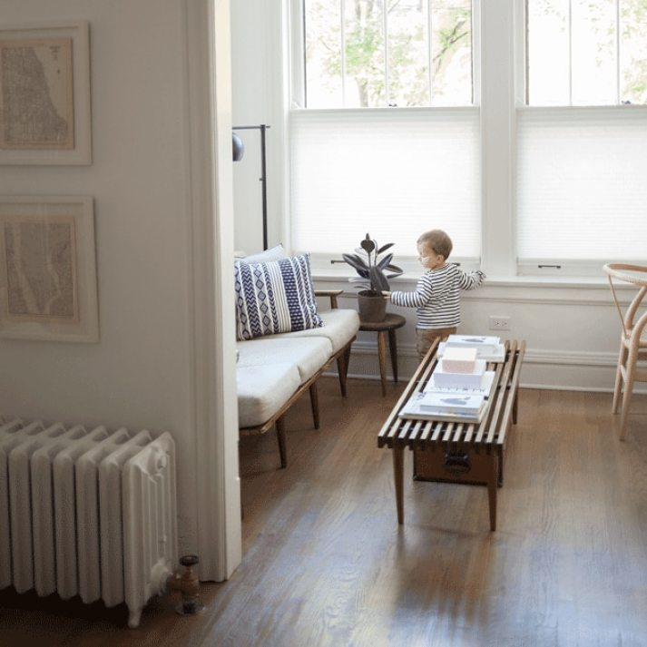 Sitting room with mid-century furniture and toddler boy standing in front of window with white top down bottom up cellular shades