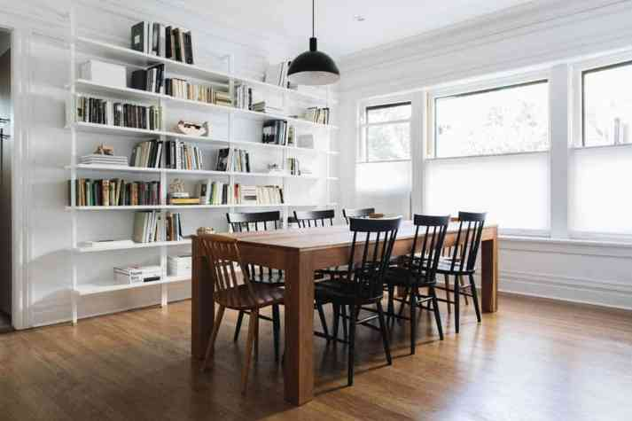 modern minimalist dining room with triple windows and white cellular shades lowered halfway down from top