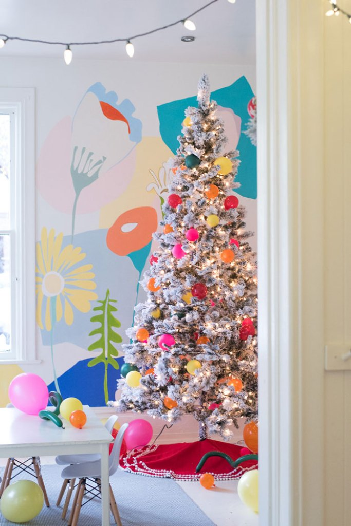 Kids' playroom decorated for christmas with colorful floral mural and flocked christmas tree with balloons as ornaments