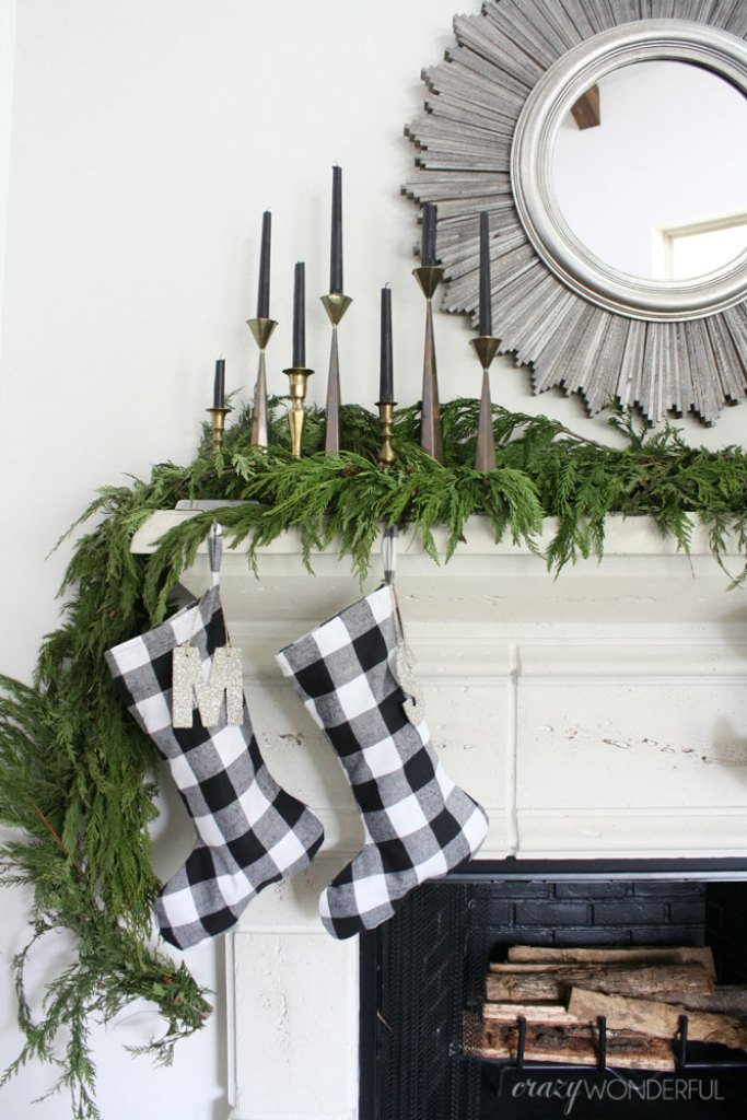 Christmas mantle with evergreen garland, modern candlesticks and buffalo plaid stockings