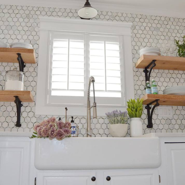 romantic kitchen with hexagonal tile backsplash, open shelving, farmhouse sink, industrial faucet and white plantation shutters on window over sink