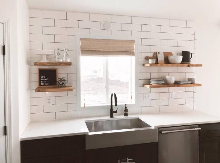 modern kitchen with stainless steen apron sink, matte black faucet, floating shelves and light brown woven wood shades on window