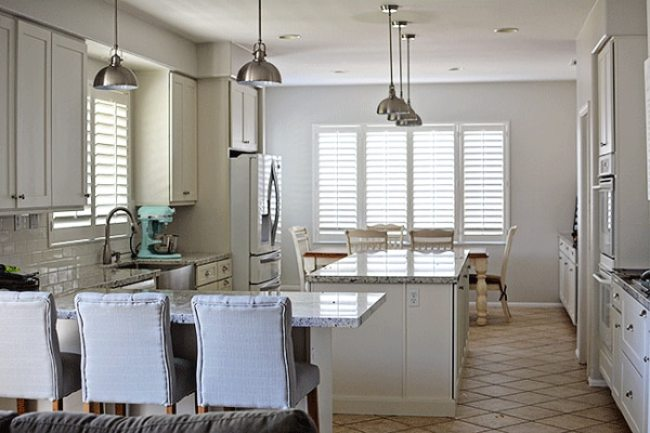 modern industrial kitchen with granite countertops, stainless steel pendant lights and plantation shutters on windows