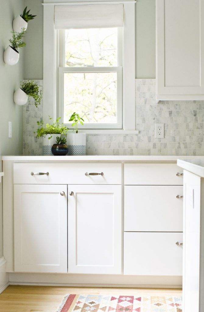White kitchen with stainless steel hardware, marble mosaic backsplash and white fabric roman shade on window