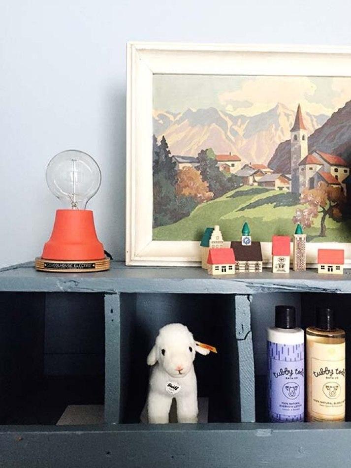 Closeup of vignette in baby boy nursery with mountain painting, red Edison bulb light and storage for toys and supplies.