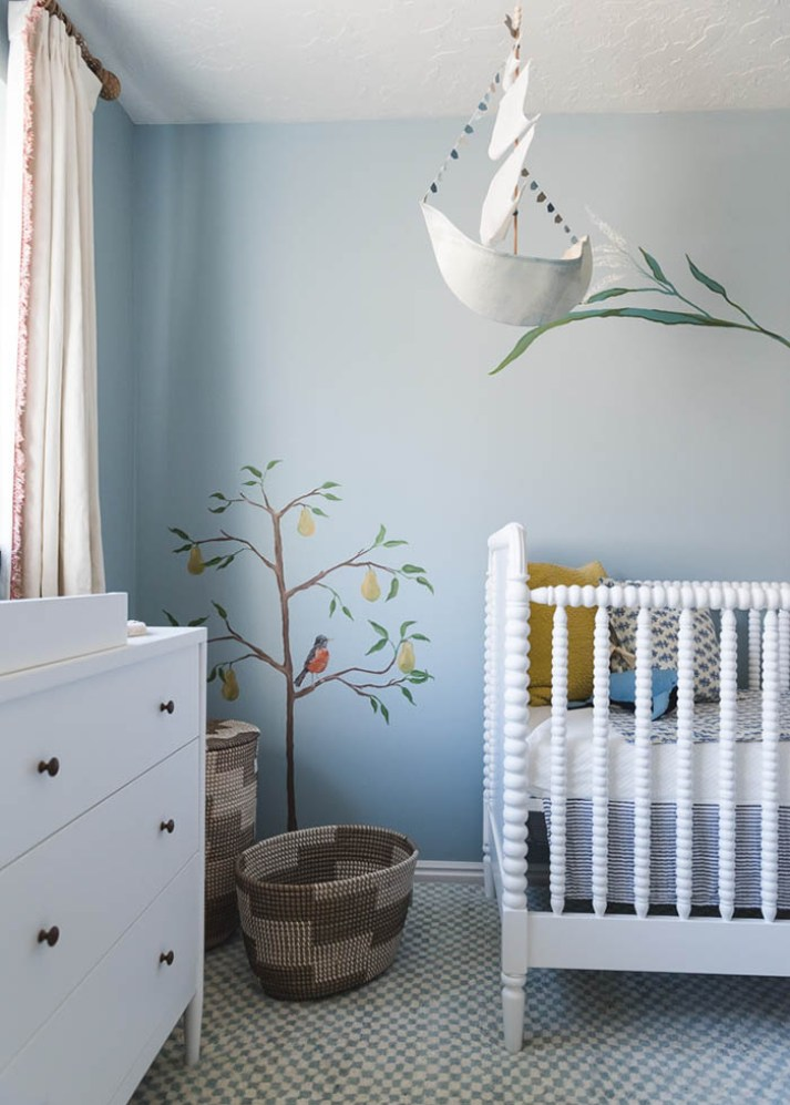 Closeup of nursery with white painted wood crib, pear tree and bird mural painted on wall and ship mobile