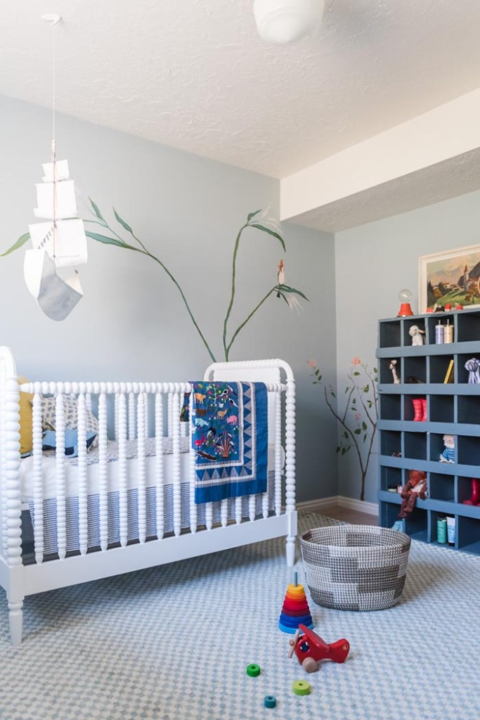 Corner of nursery with white crib, floral wall mural and navy blue cubby furniture with storage for toys.