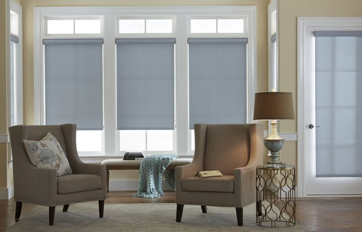 blue roller shades in three living room windows and patio door