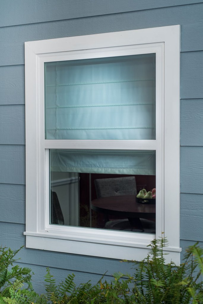 Roman Shades with white lining from outside of home