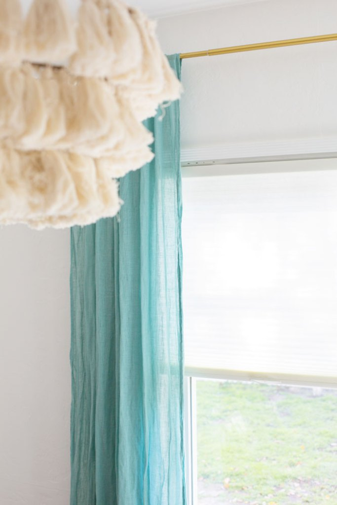 white cellular shades in dining room with teal sheer draperies layered on top and fringe chandelier