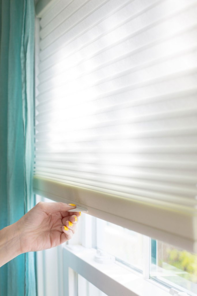 hand raising white cordless cellular shades