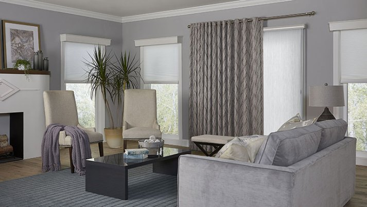 contemporary living room with white vertical cellular shades and grey curtains over sliding glass door