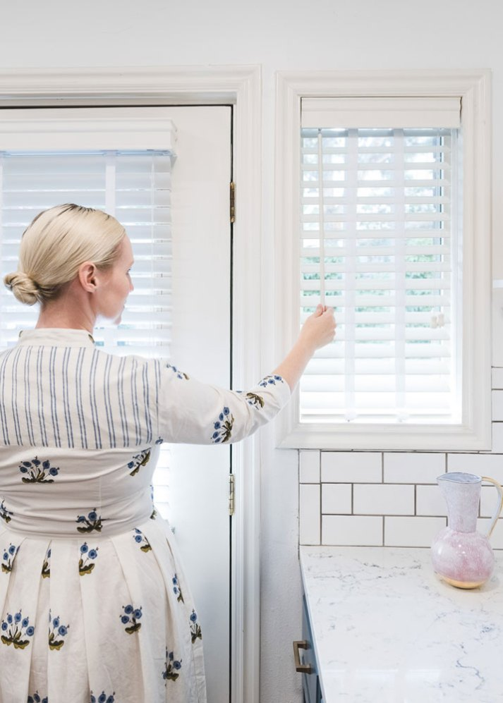 woman in blue and white dress standing in front of kitchen window tilting open white blinds