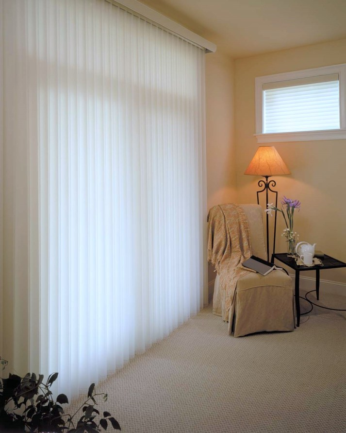 bedroom with sliding patio door and white sheer vertical shades tilted open so light shines through