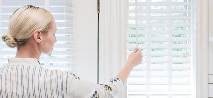 woman in white and blue dress tilting open white wood blinds