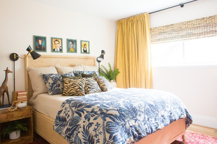 Guest bedroom with woven rattan bed frame, blue and white floral comforter, bamboo blinds and mustard yellow pleated curtains