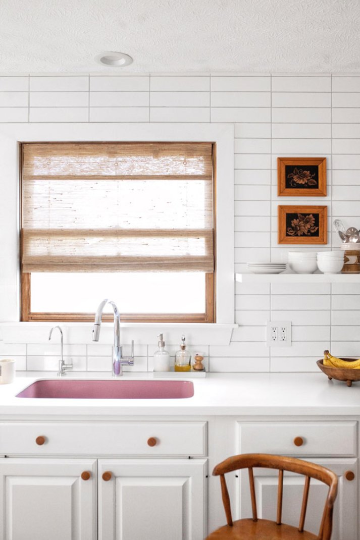 1970s inspired kitchen with withe cabinets, stained wood knobs, sheer woven window shade and pink undermount sink.