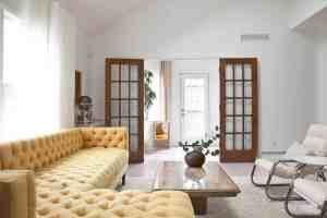 large living room with tufted yellow sectional facing wall with stained wood french doors