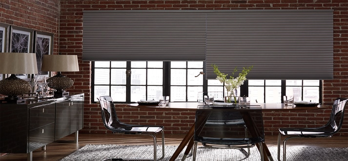 cellular shades hang over a wide window in home office