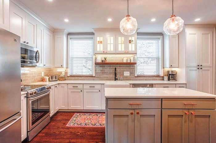 farmhouse kitchen with beige subway tile, grey cabinets on island, geometric pendant lights and white faux wood blinds.
