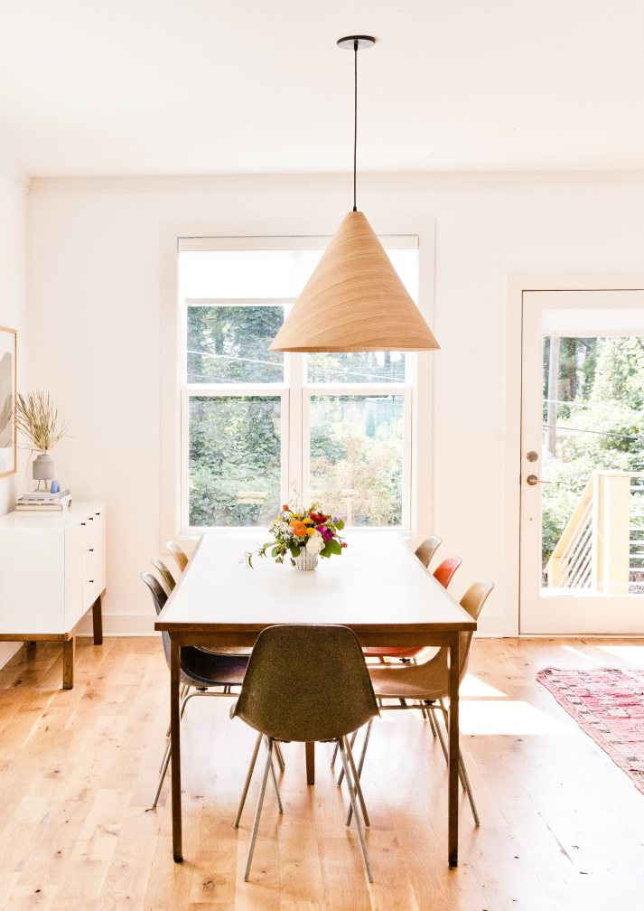 mid century dining room with large antique table, molded plastic chairs in mismatched colors and sheer white window shades with modern valance