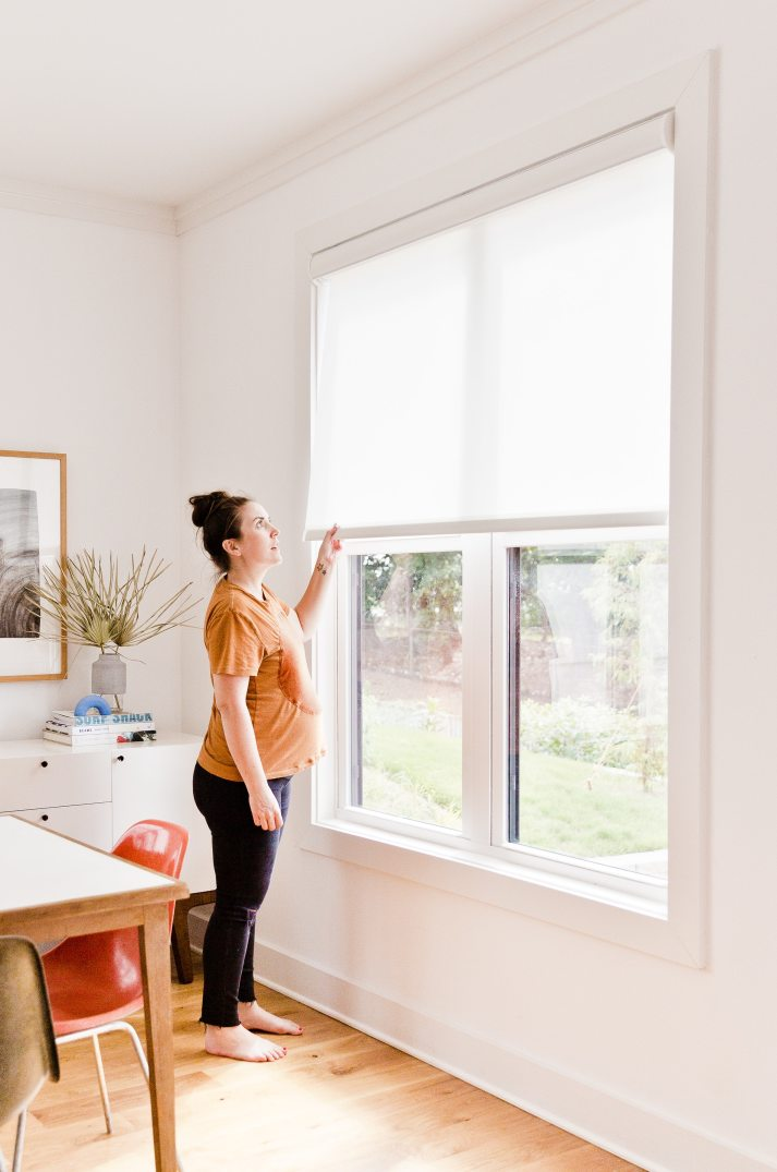 Pregnant woman opens cordless white roller shades on large window