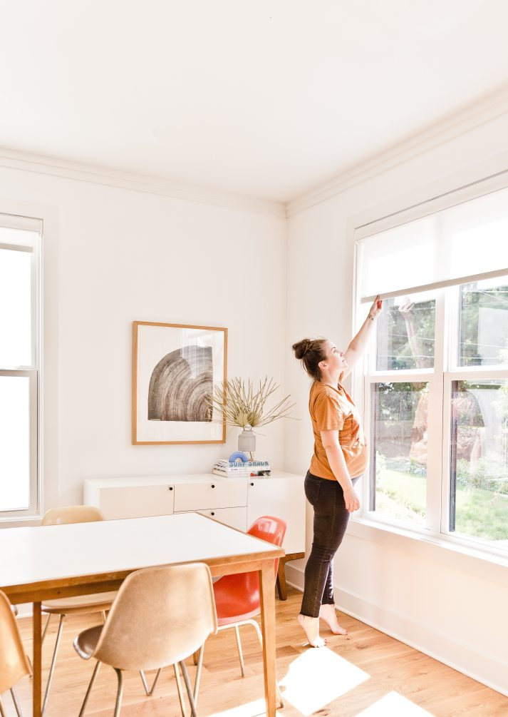 woman reaching to lower cordless roller shades on large window in mid century dining room