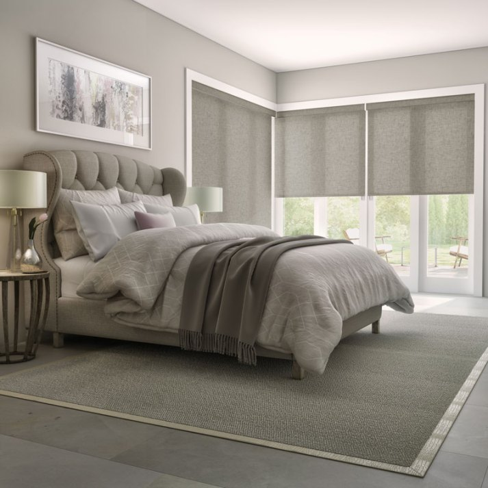traditional bedroom in neutral palette with grey upholstered bed and corner windows with grey fabric roller shades from levolor