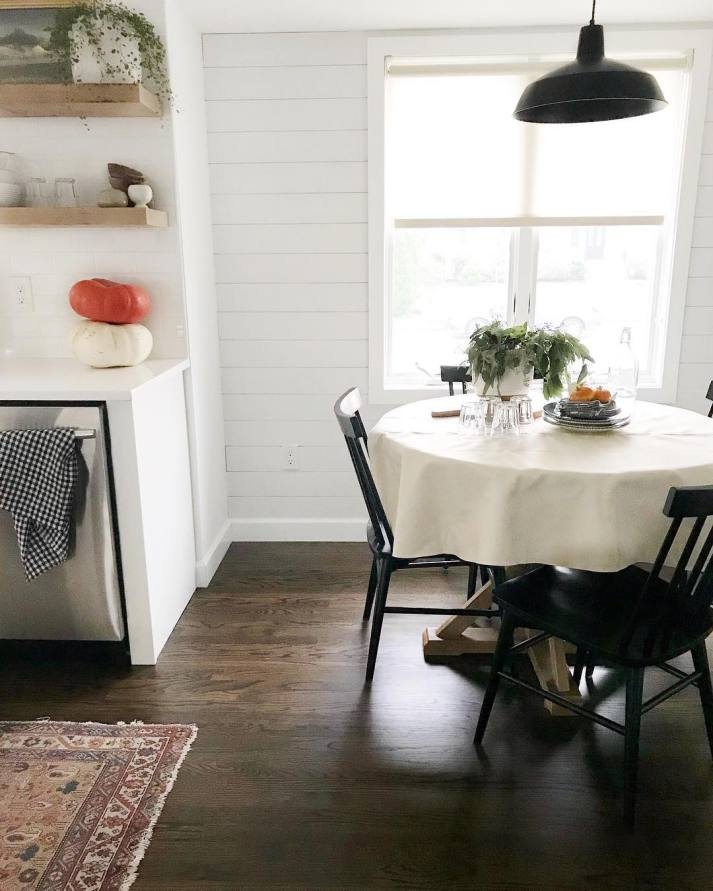 kitchen decorated for fall with pumpkins on counter, greenery centerpiece and white roller shades on window behind table.
