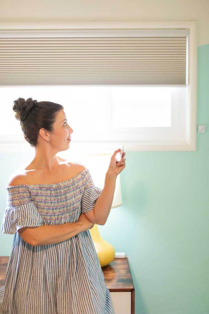 woman opening grey remote controlled window shades in kids bedroom