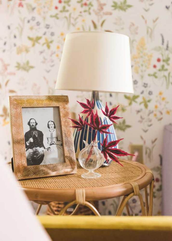 Small rattan table with blue and white ceramic lamp and picture frame with vintage portrait.