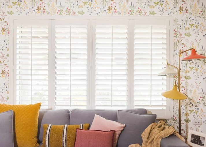 living room window with white plantation shutters, floral wallpaper and colorful vintage lamp
