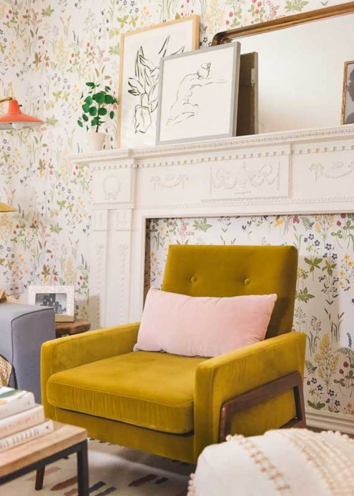 Living room with colorful floral wallpaper and faux fireplace mantel leaned against wall with mustard velvet chair