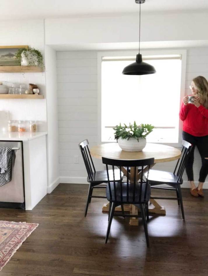modern farmhouse kitchen nook with round table, black chairs and sheer white roller shade in window.