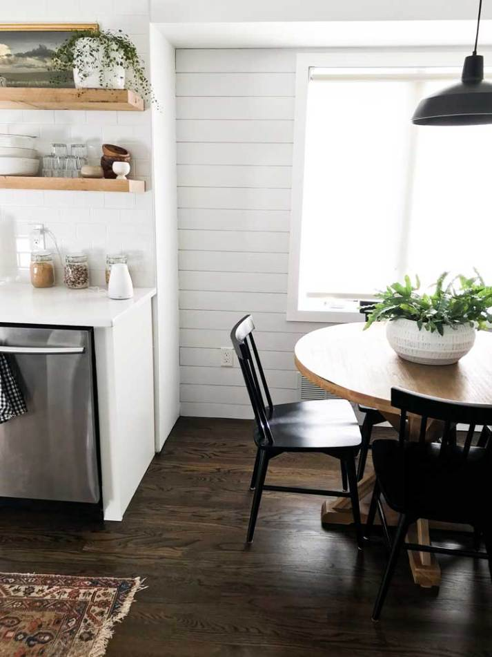 white kitchen with light wood floating shelves and round table with black windsor chairs in front of window with light streaming in