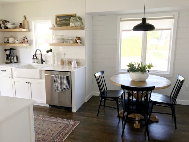 farmhouse kitchen with floating shelves, subway tile, farmhouse sink and breakfast nook with white roller shades in sheer fabric.
