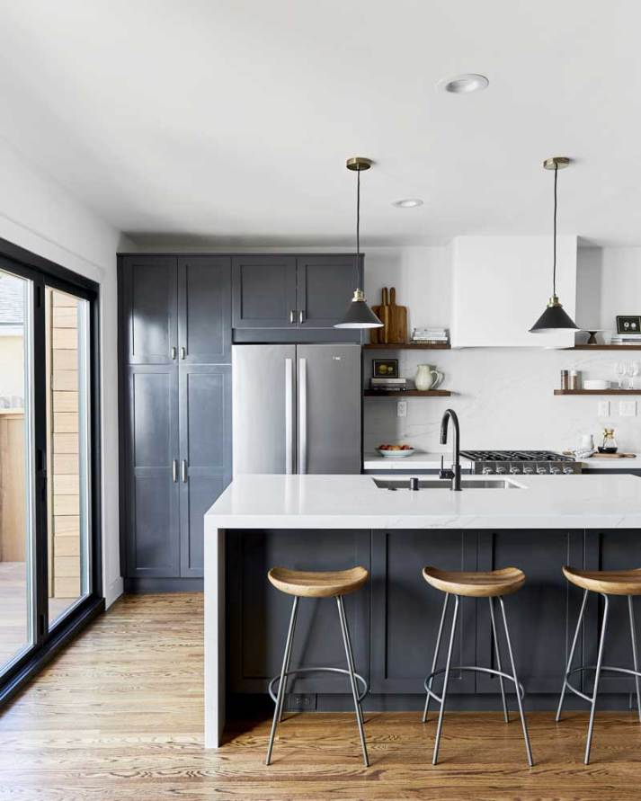 transitional kitchen with navy shaker cabinets, white marble waterfall island and bent wood and metal barstools