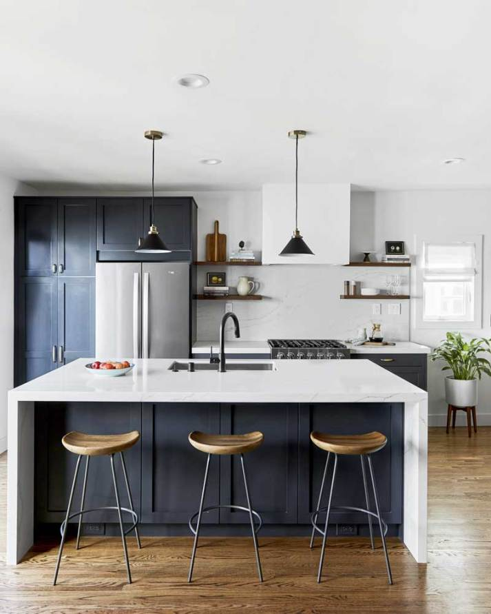 bright kitchen with navy cabinets and small window in background with white roman shade