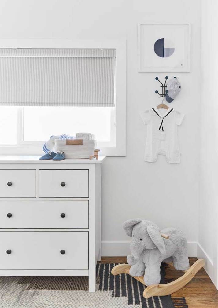 Contemporary white baby nursery with traditional dresser, rocking elephant and roller shade with grey and white pin stripes on window