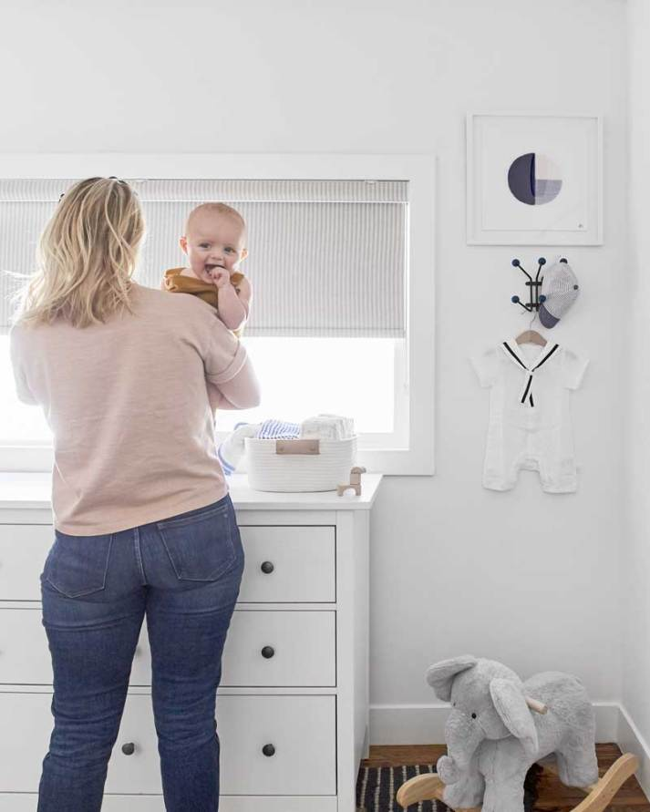 Mother holding young baby boy facing window with grey and white striped window shade
