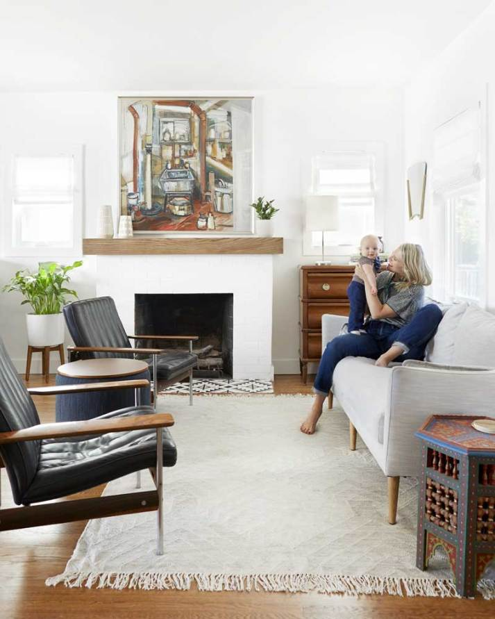 woman in contemporary white living room holding baby on couch