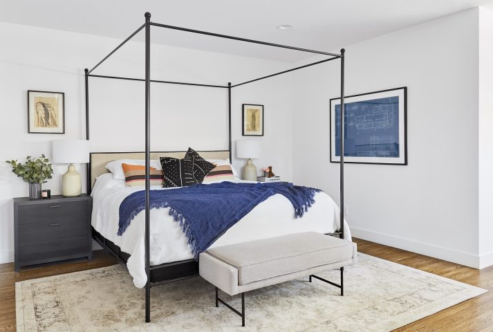 master bedroom with black metal four poster bed and navy accents