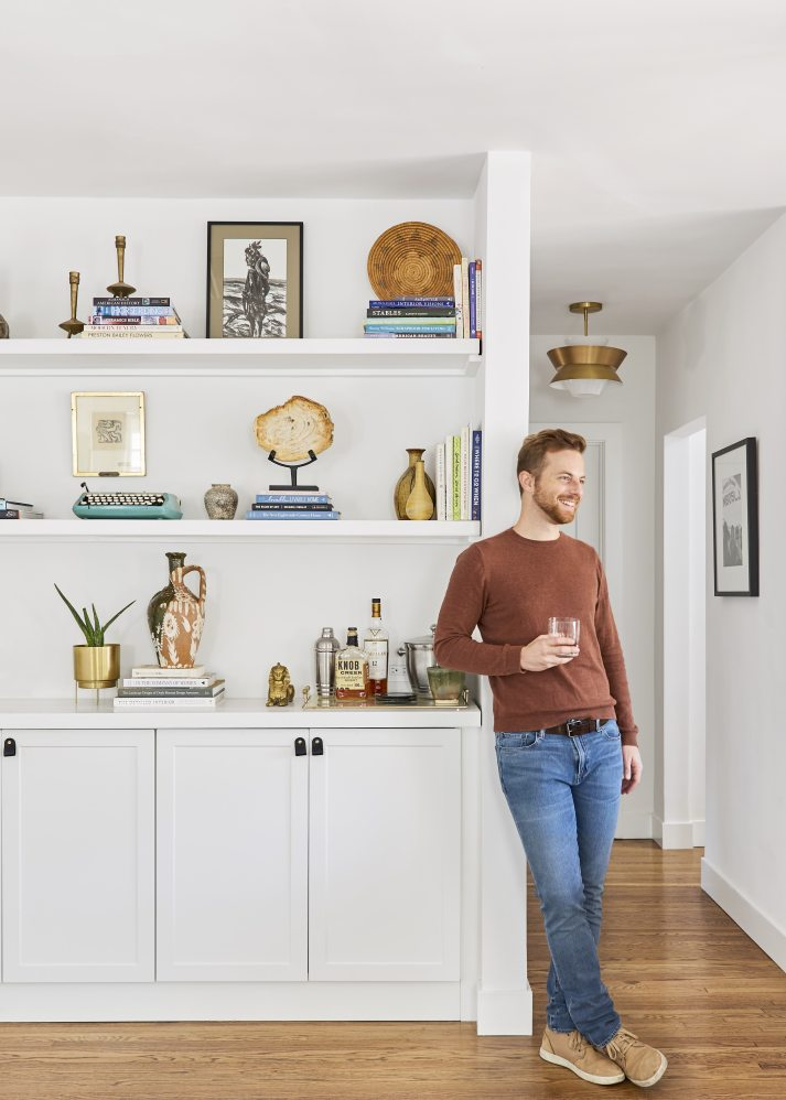 ned fulmer leaning against bookcase with stylish accessoires