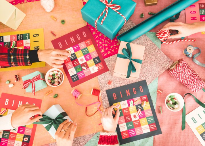 tabletop at christmas party with wrapped gifts and bingo boards in teal red and pink palette