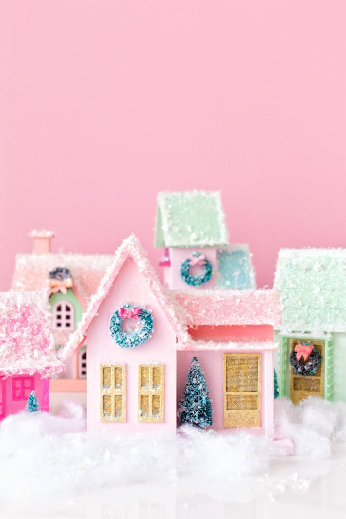 colorful homemade christmas village in bright colors with faux snow